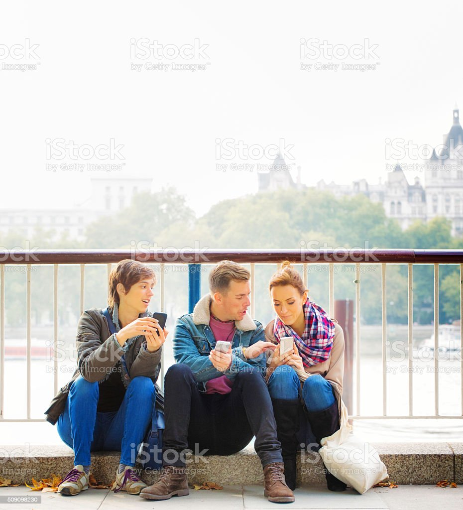 Three friends sharing media on their phones sitting by Thames stock photo