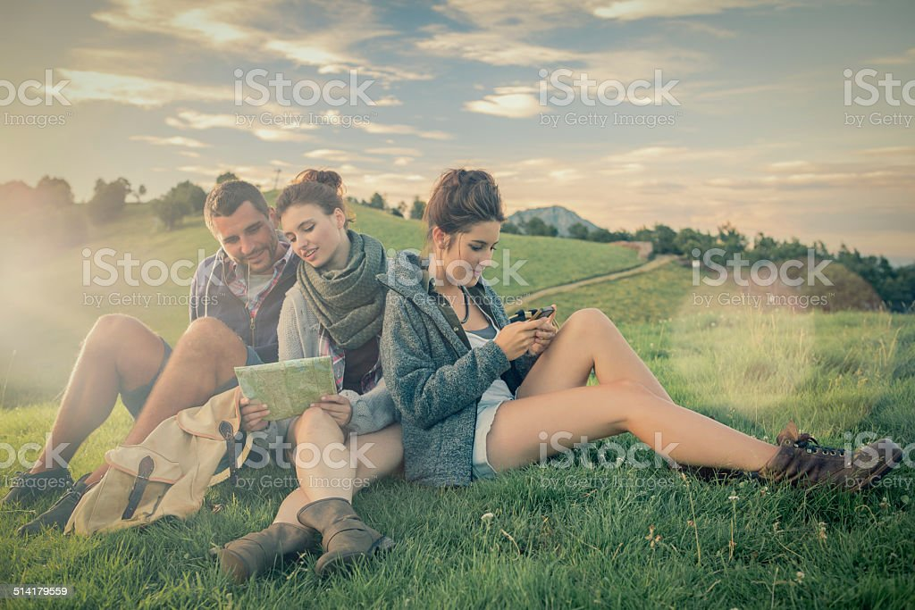 Three friends sitting on grass looking at map on mountain stock photo