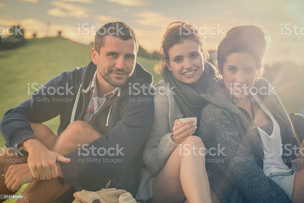 Three friends sitting on grass looking in camera on mountain stock photo