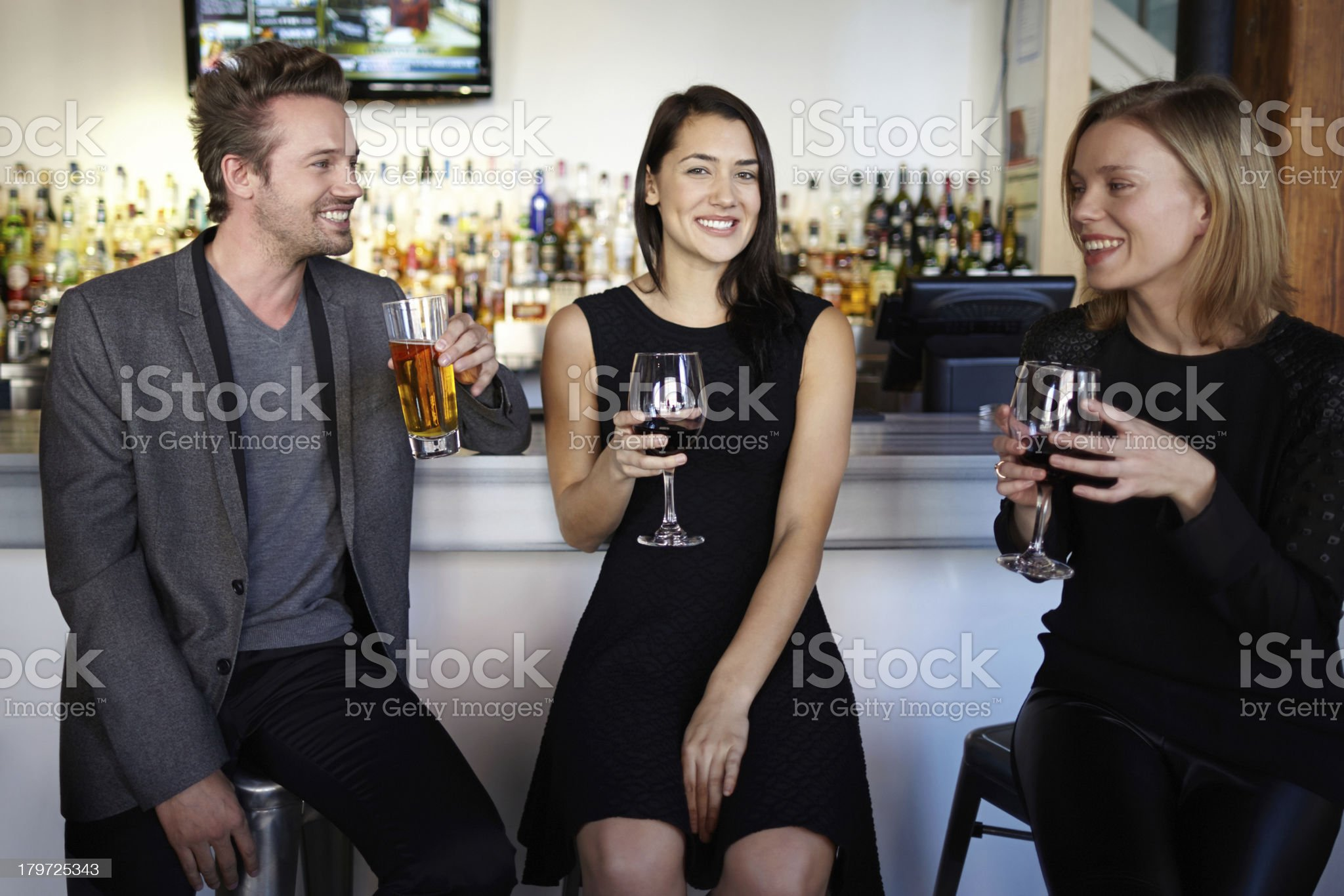 Three friends socializing and drinking at a bar counter smiling royalty-free stock photo