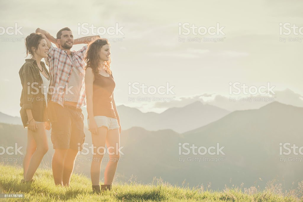 Three friends stand looking at panorama on mountain stock photo