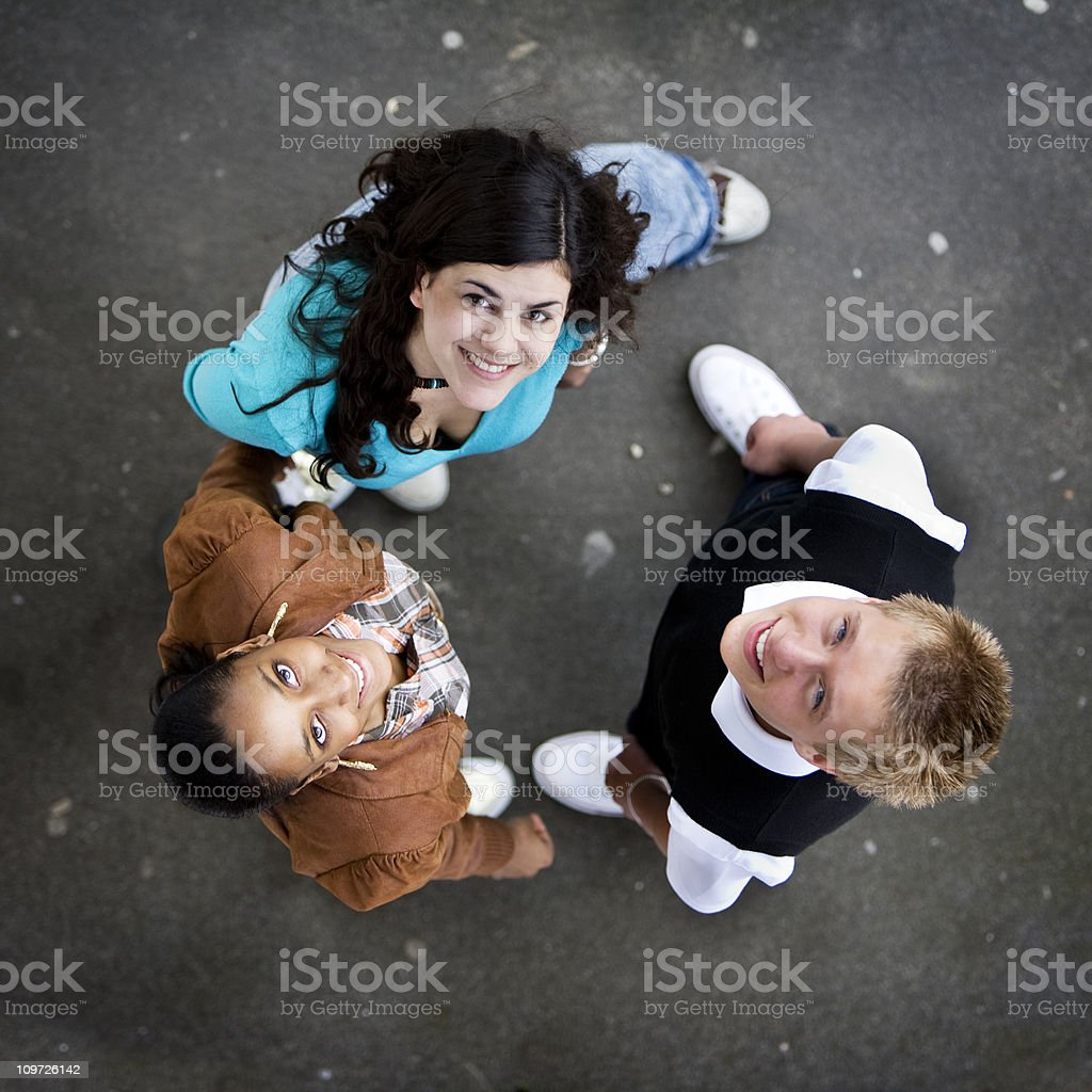 three friends standing in a circle looking up and smiling royalty-free stock photo