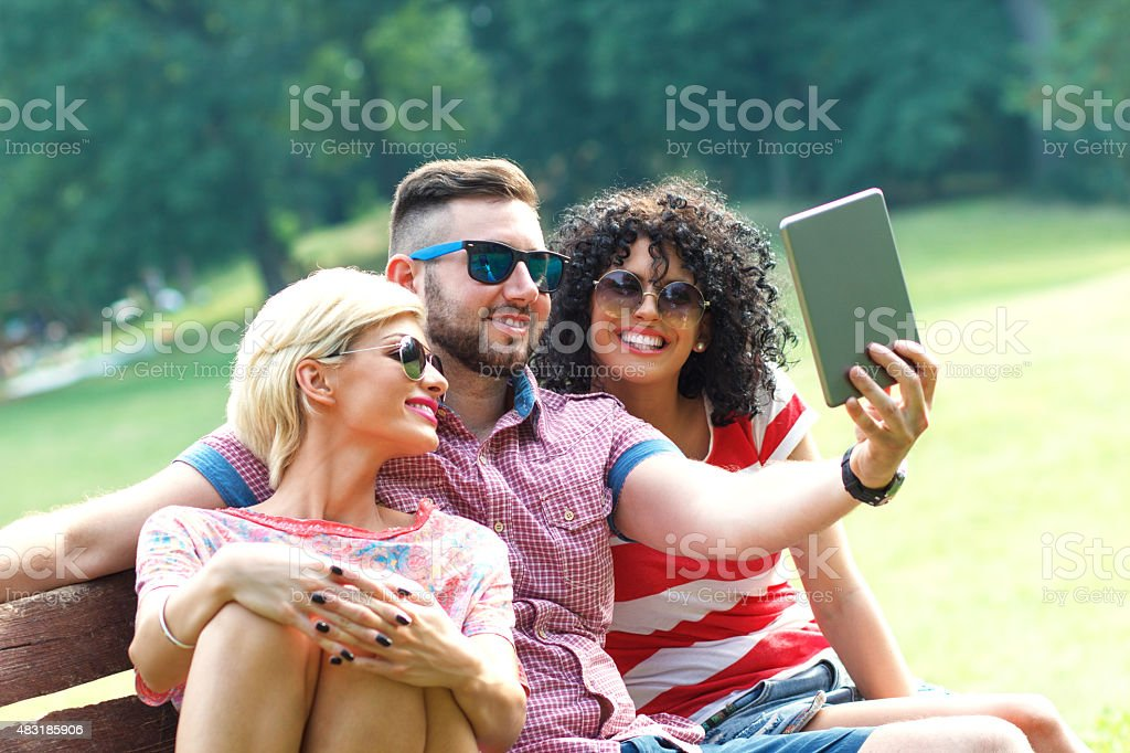 Three friends taking a selfie in park. stock photo