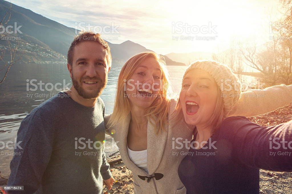 Three friends taking selfie portrait by the lake at sunset stock photo