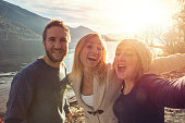 Three friends taking selfie portrait by the lake at sunset