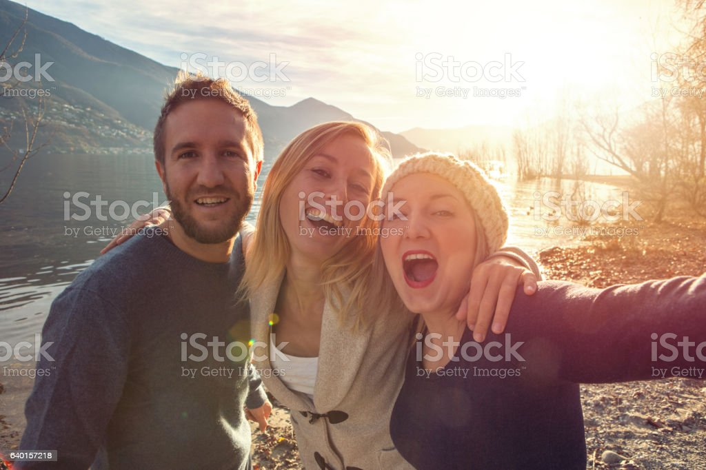 Three friends taking selfie portrait by the lake at sunset – Foto
