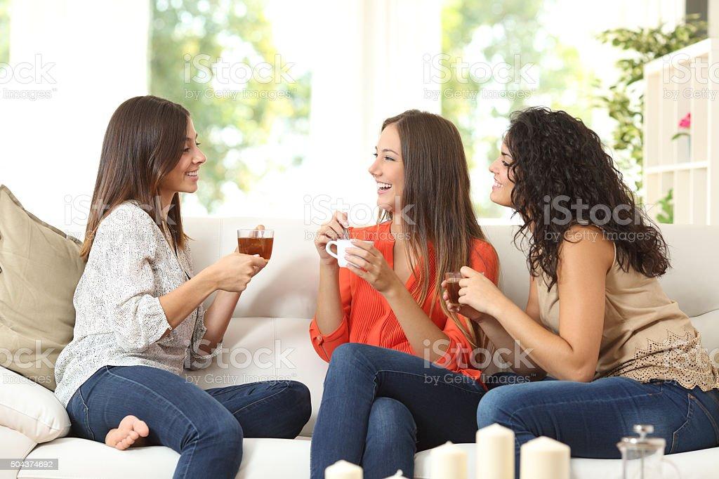 Three friends talking at home stock photo