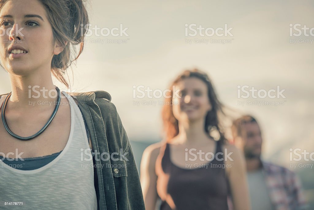 Three friends walk in nature in sunny day stock photo