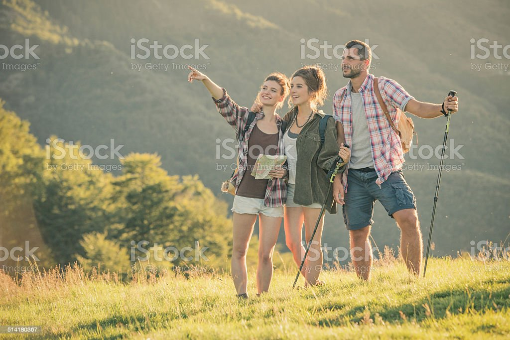Three friends walk on mountain path in sunny day stock photo