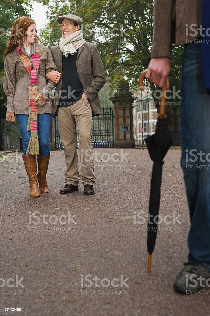 Three friends walking in park stock photo