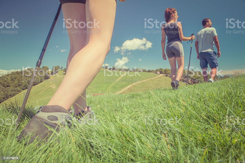 Three friends walking in sunny day on mountain outdoor stock photo