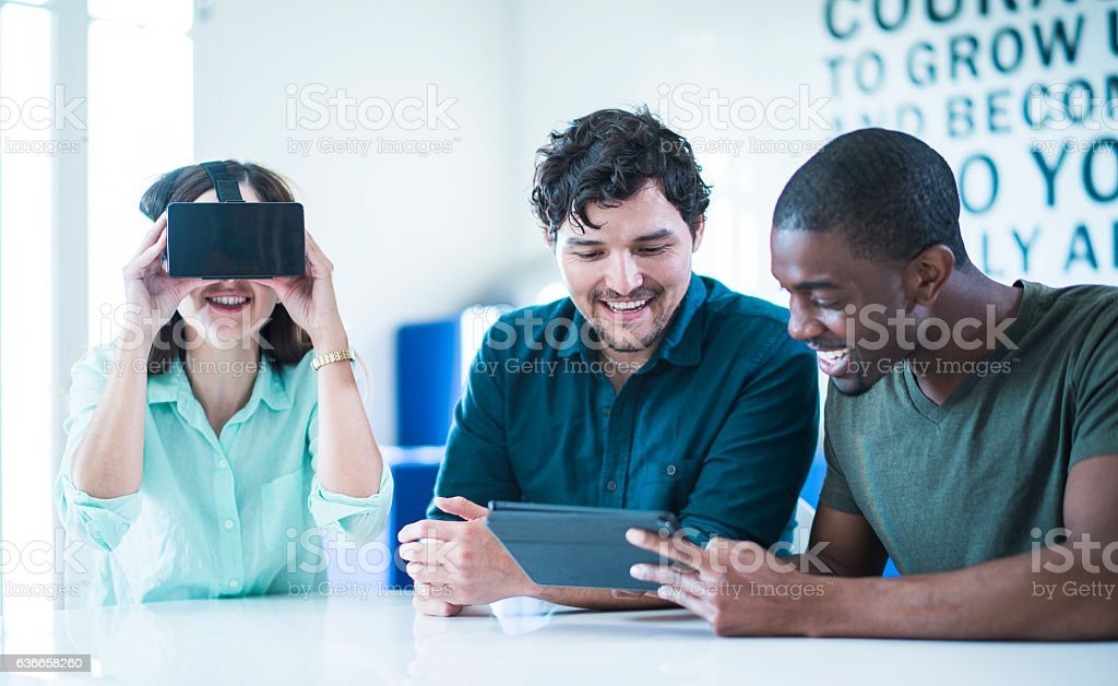 Three friends, white, black and latino, exploring virtual reality stock photo