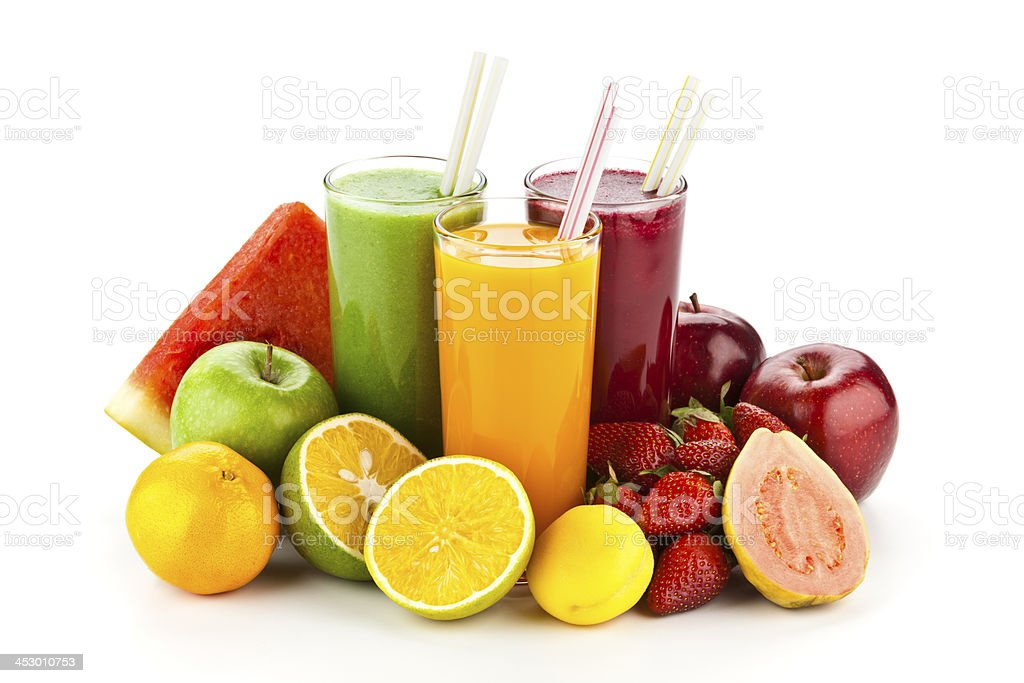 Three fruit juice glasses surrounded by colorful fruits stock photo