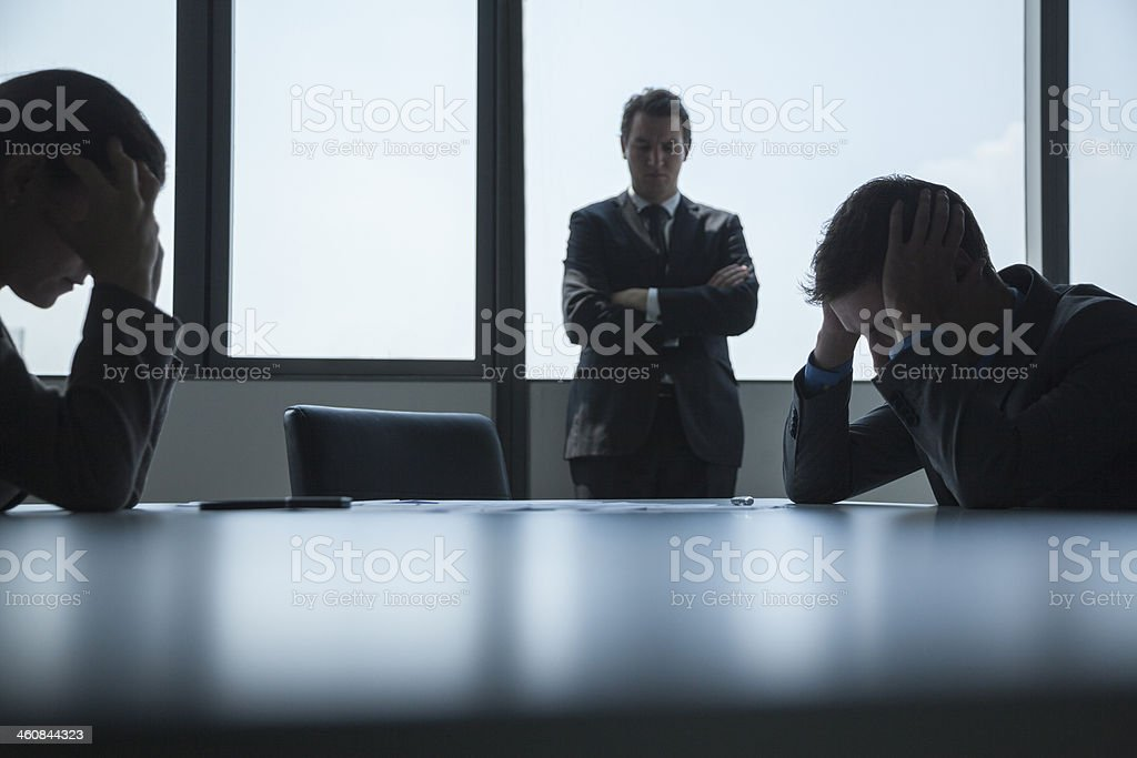 Three frustrated and overworked business people in the board room stock photo