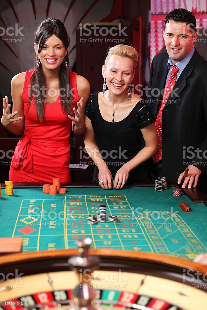 Three gamblers playing on the roulette. stock photo