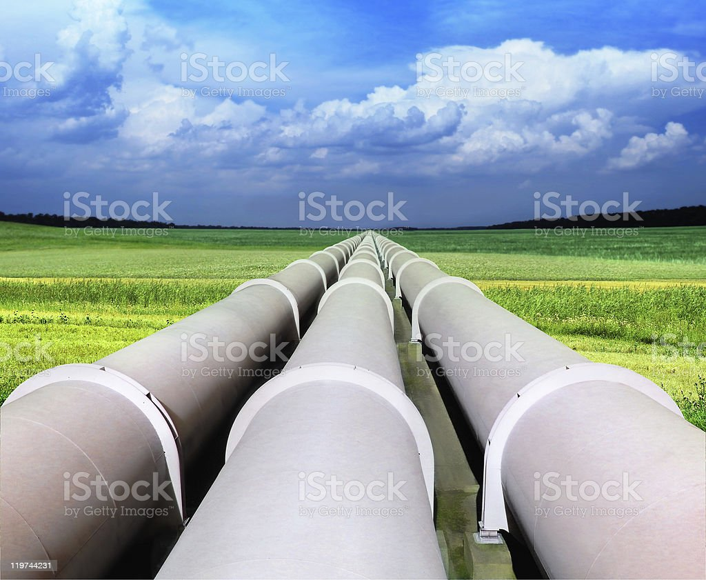 Three gas pipelines in a green field with blue sky stock photo