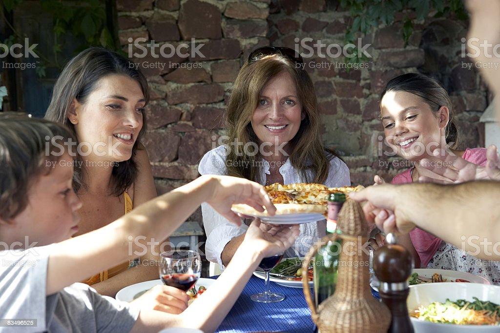 three generation family eating outdoors stock photo
