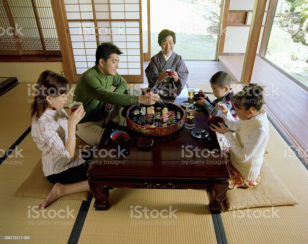 Three generation family eating sushi, elevated view stock photo