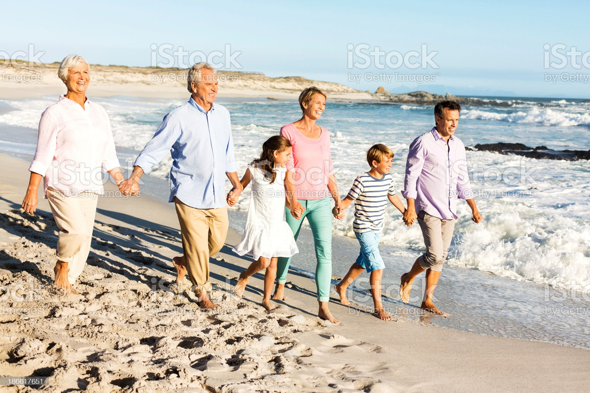 Three Generation Family Holding Hands While Walking On Beach royalty-free stock photo