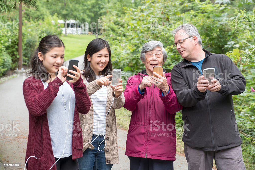 Three Generation Family Holding Smartphones to Play Augmented Reality Game stock photo