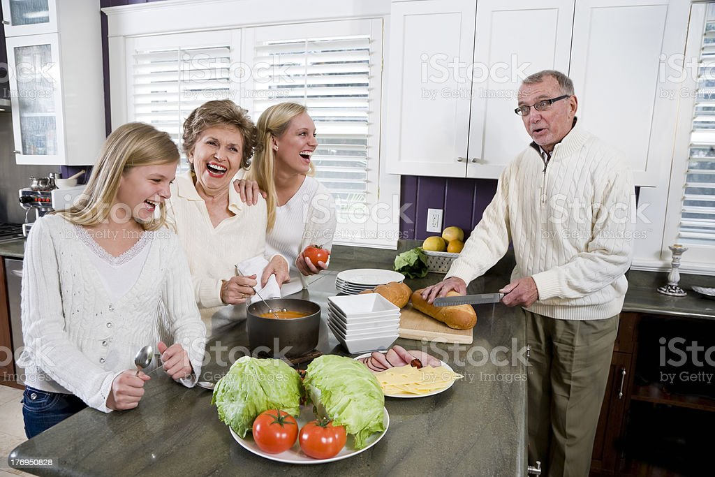 Three generation family in kitchen cooking lunch royalty-free stock photo