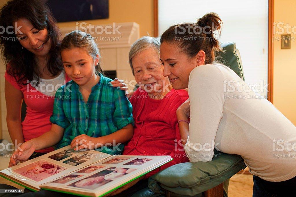 Three generation family looking at photo album stock photo