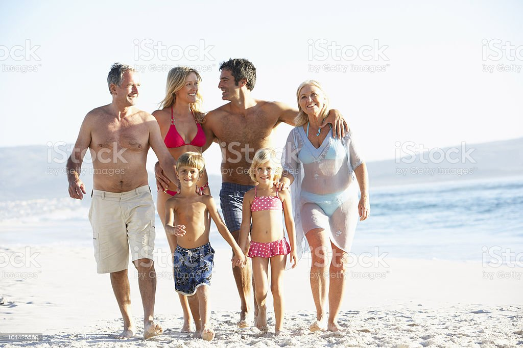 Three Generation Family On Holiday Walking Along Beach royalty-free stock photo