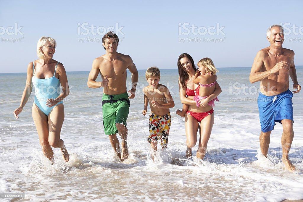 Three generation family playing on beach royalty-free stock photo