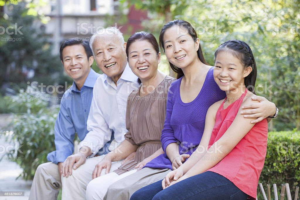 Three Generation Family Sitting in their Apartment Courtyard stock photo