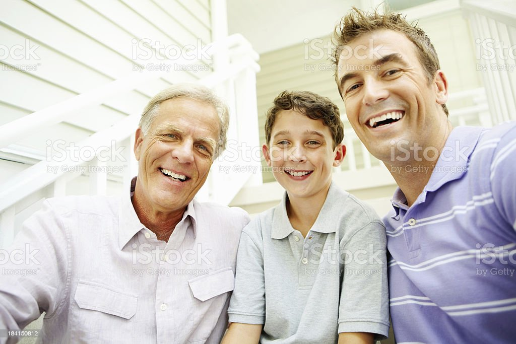 Three generation family sitting on staircase and smiling royalty-free stock photo