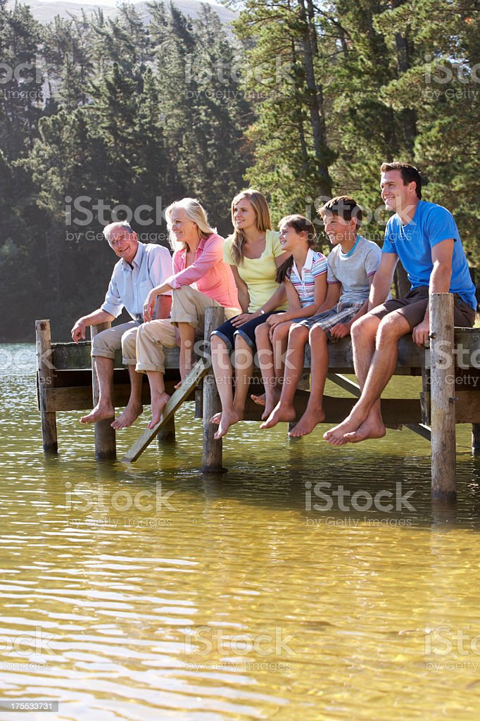 Three Generation Family Sitting On Wooden Jetty Looking Out Over stock photo