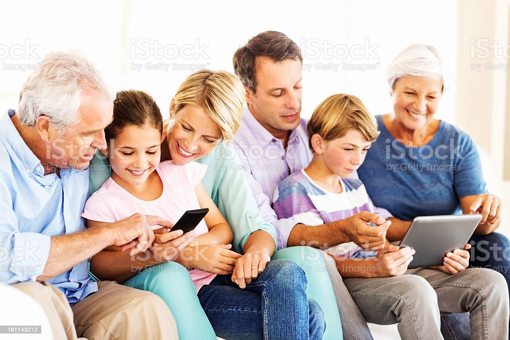 Three Generation Family Using Smart Phone And Digital Tablet royalty-free stock photo