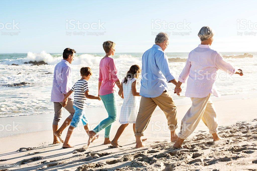 Three Generation Family Walking Holding Hands On Beach royalty-free stock photo