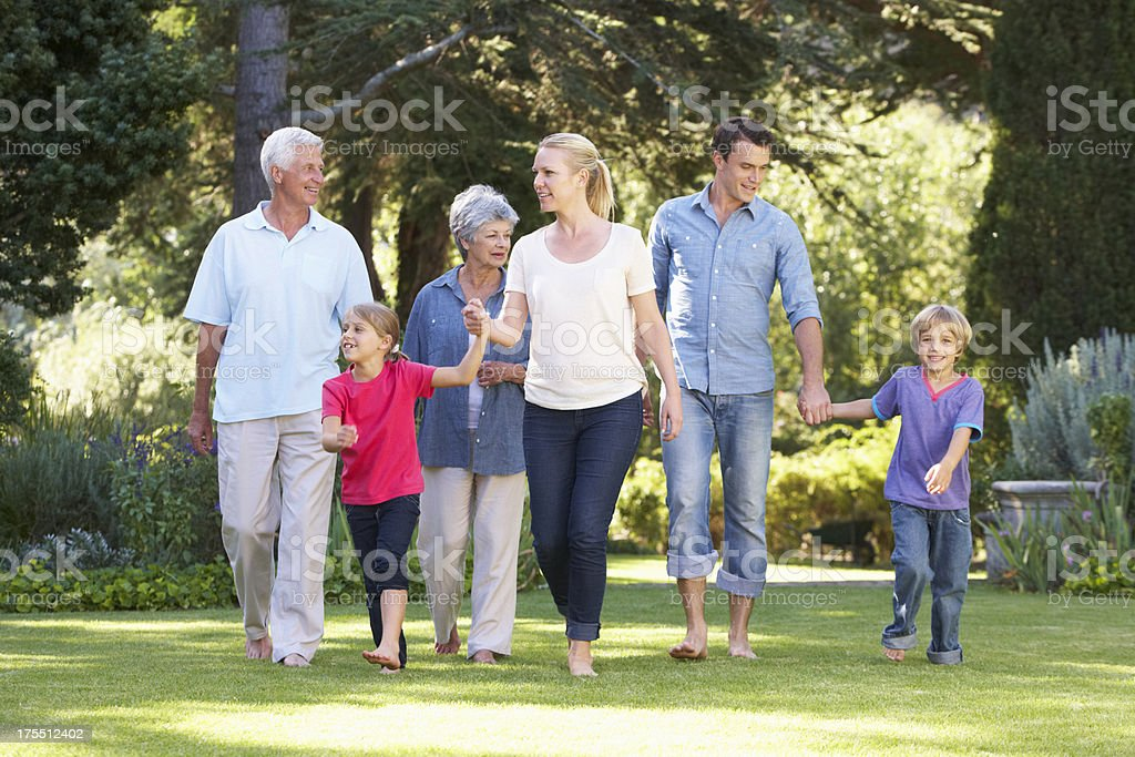 Three Generation Family Walking In Garden Together royalty-free stock photo