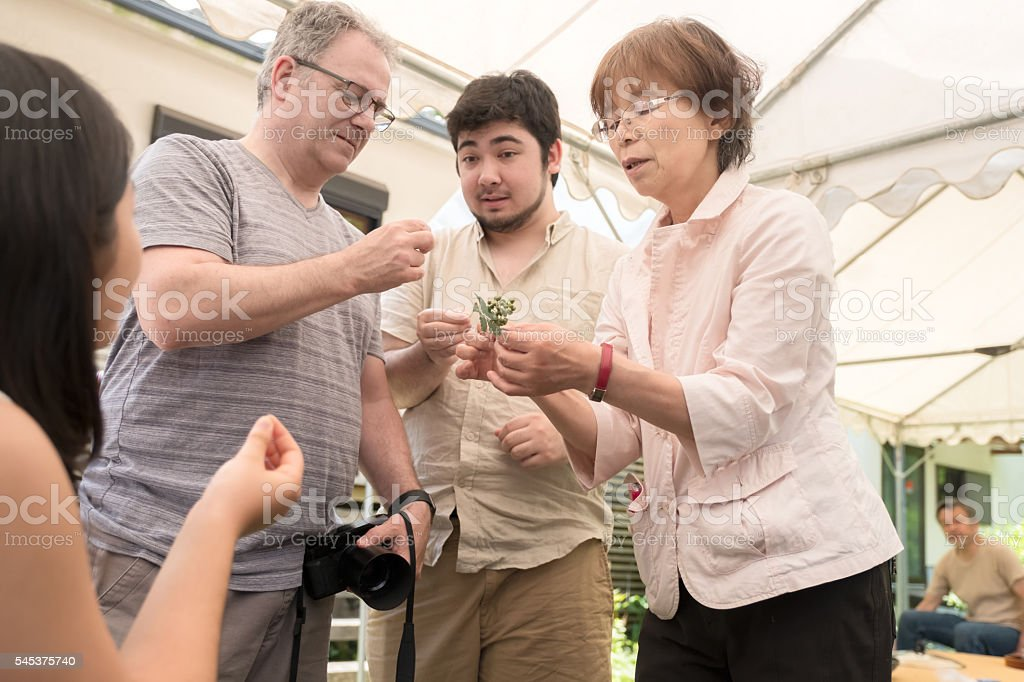 Three Generation Interracial Family Learning about Edible Japanese Pepper Plant stock photo