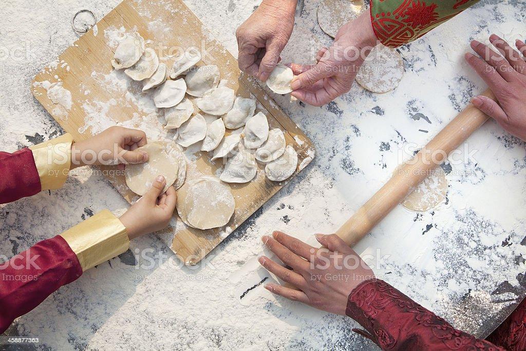 Three generation of women making dumplings, hands only stock photo