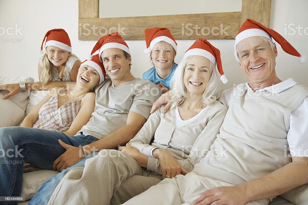 Three generational family sitting together wearing Santa's cap royalty-free stock photo