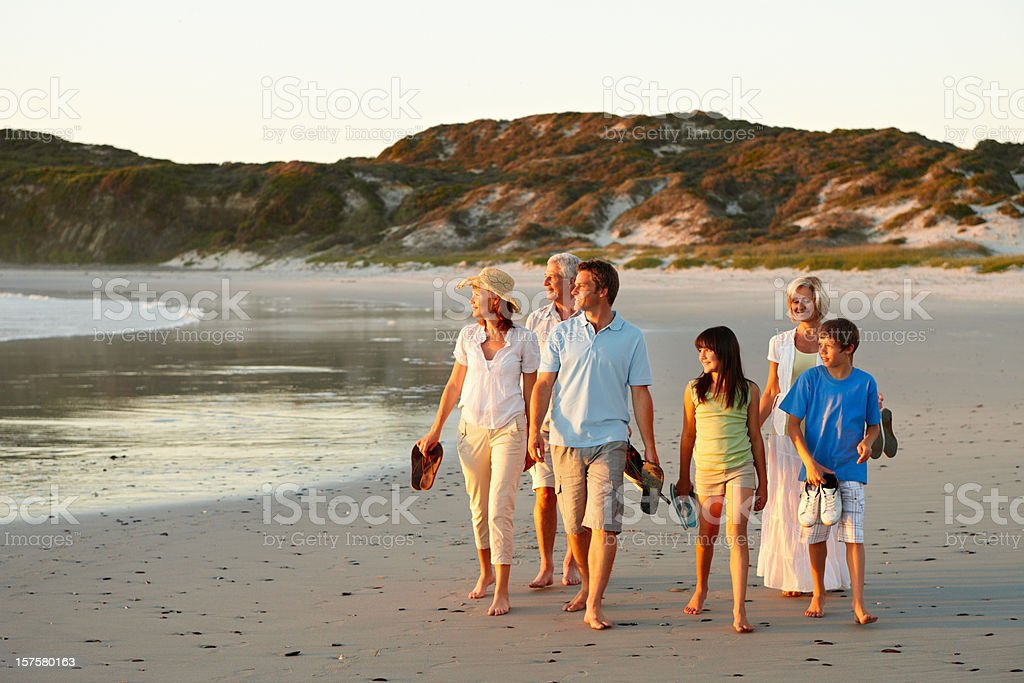 Three generational family walking together on beach royalty-free stock photo