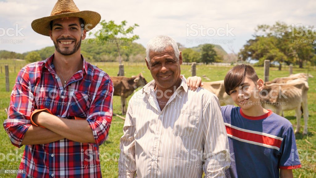 Three Generations Family Portrait Of Farmers In Farm stock photo