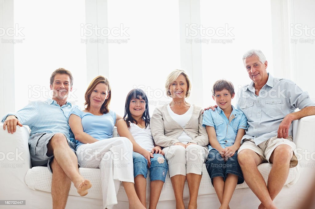 Three generations of a family sitting together on couch royalty-free stock photo