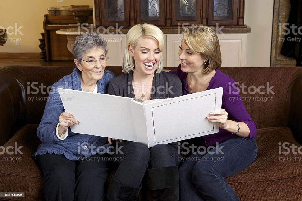 Three Generations of Beautiful Women Looking at a Photo Album royalty-free stock photo
