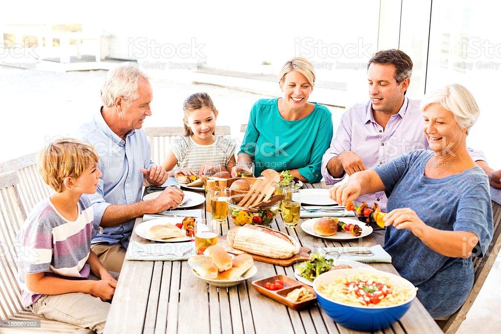 Three Generations Of Family Enjoying Lunch Al Fresco royalty-free stock photo