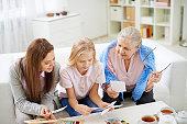 Three generations of females looking at family photos