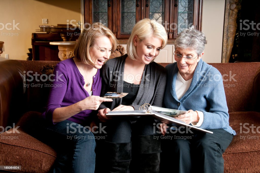 Three Generations of Woman Looking At Family Photos stock photo