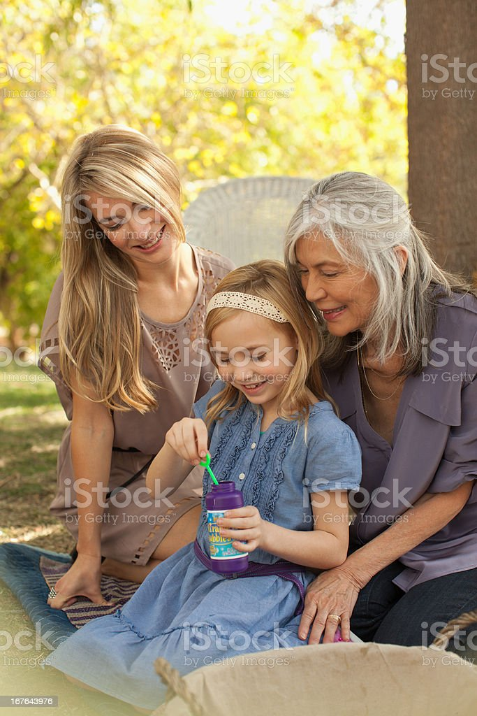 Three generations of women blowing bubbles royalty-free stock photo