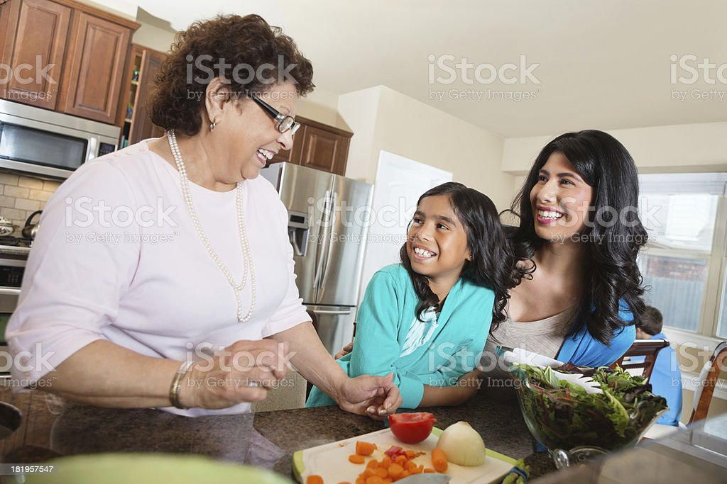 Three generations of women preparing dinner in family kitchen royalty-free stock photo