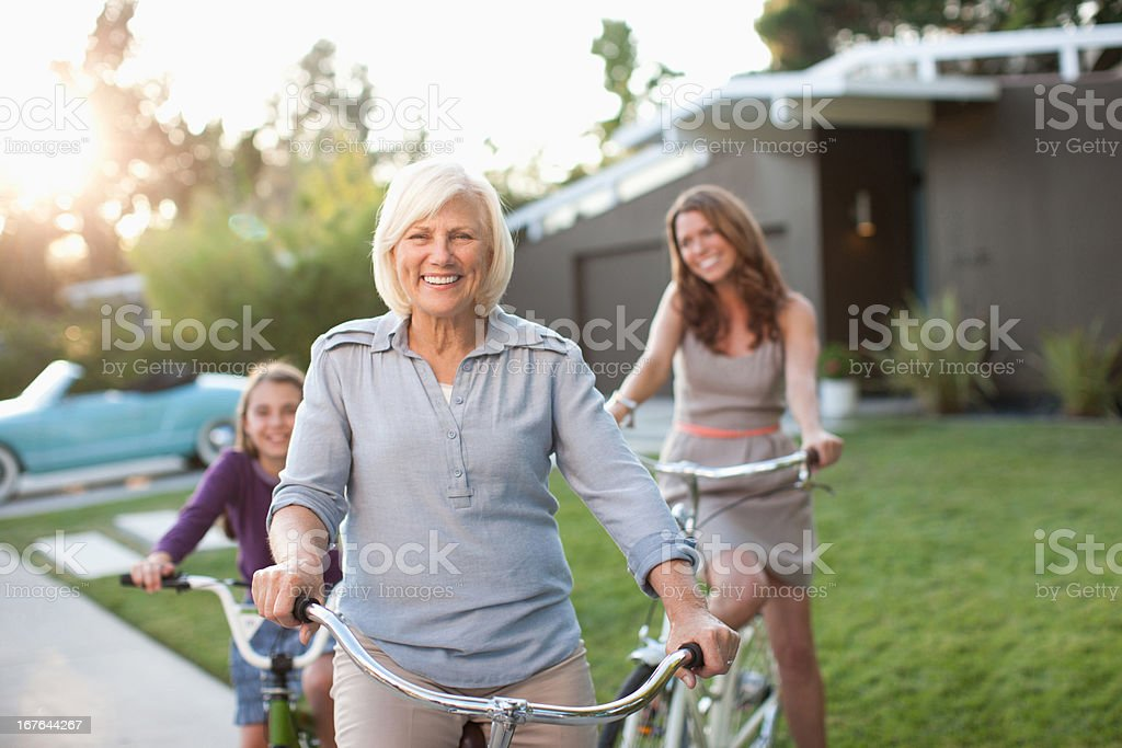 Three generations of women riding bicycles stock photo