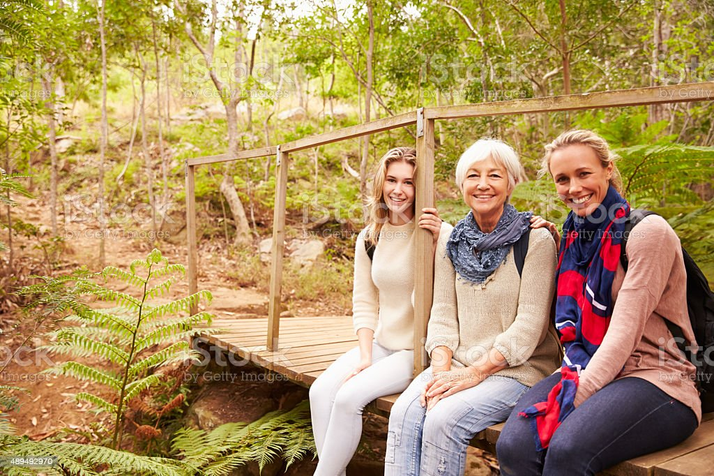 Three generations of women sitting in a forest, portrait stock photo