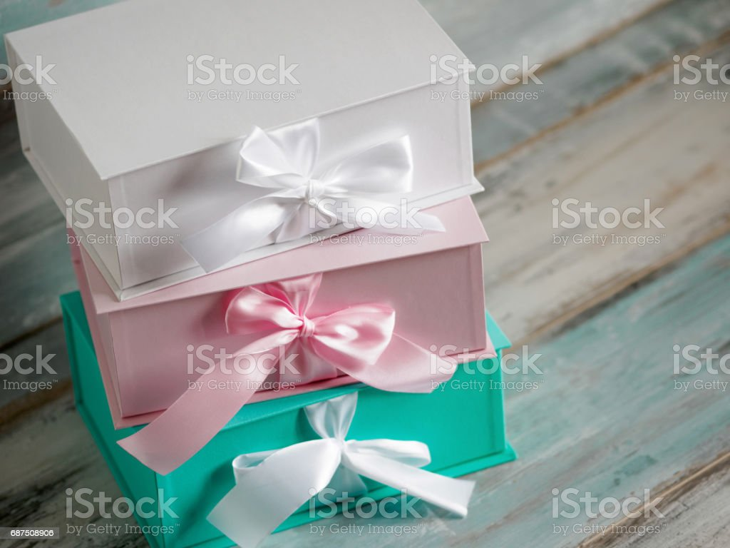 Three gift boxes, white, pink and turquoise. Top view diagonally on a wooden background. Gifts for your girlfriend stock photo