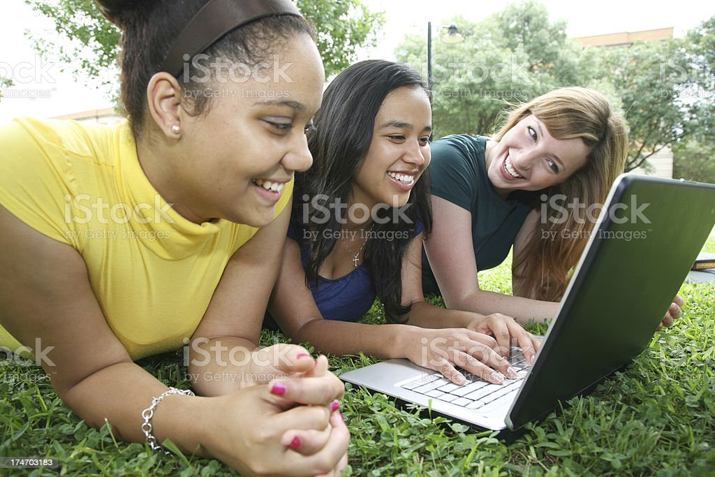Three Girl Friends Happily Working on a Laptop royalty-free stock photo